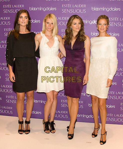 "HILARY RHODA, GWYNETH PALTROW , ELIZABETH HURLEY & CAROLYN MURPHY .Worldwide Debut of Estee Lauder's Newest Fragrance ""Sensuous"".at Bloomingdale's, New York, NY, USA, July 8, 2008..photocall Estee models faces full length black split sleeve shoulder dress cream white ruffle neck dresses purple aubergine perfume gladiator heels sandals shoes Liz.CAP/LNC/TOM.©LNC/Capital Pictures"