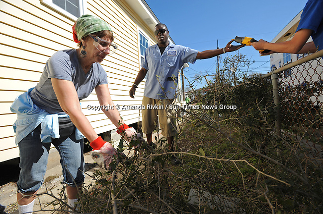 """Patti Vile, 65, of Glencoe, Ill. and Tron Lee, 23, of Destrahan, Louisiana prune a bush outside the new home of Aniece Gibbs, 89, in the Hollygrove section of New Orleans, La. on March 10, 2008.  The group of """"voluntourists"""" led by Vile from Glencoe, Illinois is traveling to New Orleans to combine traditional tourism with volunteer work in the aftermath of the devastation wrought by Hurrica Katrina in 2005."""