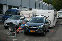 Switzerland. Canton Ticino. Tenero. Waiting place outside Camping Campofelice. Motorhomes and caravans wait on line to enter the campsite as soon as a free place will be available.A couple of Dutch tourists are resting seated on a chair and enjoy a drink in the late afternoon. A campervan (or camper van), sometimes referred to as a camper, or a caravanette, is a self-propelled vehicle that provides both transport and sleeping accommodation. A motorhome (or motor coach is a type of self-propelled recreational vehicle (RV) which offers living accommodation combined with a vehicle engine. Motorhomes are part of the much larger associated group of mobile homes which includes caravans, also known as tourers, and static caravans. A caravan, travel trailer, camper or camper trailer is towed behind a road vehicle to provide a place to sleep which is more comfortable and protected than a tent. It provides the means for people to have their own home on a journey or a vacation. Campers are restricted to designated sites for which fees are payable. 19.07.2018 © 2018 Didier Ruef