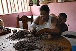 Sabina, una de las artesanas del pueblo, esta machacando la almendra de cacao tostado  para sacar la piel.  Chuao. Estado Aragua. Venezuela. © Juan Naharro