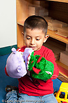 Education preschool 3-4 year olds boy playing alone with two hand puppets talking and pretending vertical