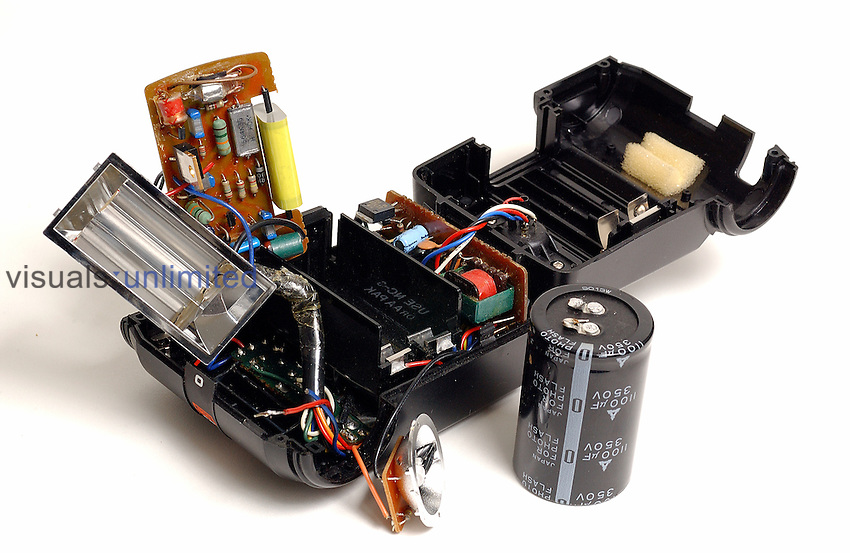 View of a disassembled flash unit. The cylindrical xenon flash tube is shown on the left in its reflective housing. The capacitor (large, black cylinder) that stores energy for the flash discharge has been disconnected and is shown in the middle foreground.  Other components associated with triggering the discharge and providing electrical power are shown on the circuit boards. Caution: Don't disassemble a flash unit yourself, Could cause serious injury or death from electrical shock.