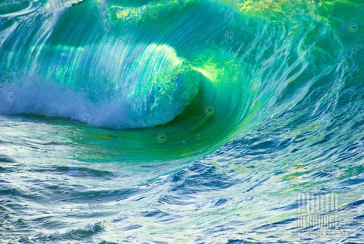 A large glowing shorebreak wave barrels onto the beach at Ke Iki beach, on the North Shore of Oahu.