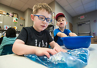 NWA Democrat-Gazette/BEN GOFF @NWABENGOFF<br /> Braxton Strode (left), 4, of Rogers feels a bag full of gel as Mason Virden, 3, of Lowell dips his hands into a bowl of water-absorbing balls Wednesday, Feb. 7, 2018, during a 'Hands On!' sensory program for ages 0-12 at the Rogers Public Library. The program offered a variety of toys and materials for children to explore and make crafts.