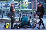 © Joel Goodman - 07973 332324 . 07/04/2017 . Manchester , UK . Paramedics helping a man , lying collapsed on the pavement on Piccadilly Gardens . Greater Manchester Police have authorised dispersal powers and say they will ban people from the city centre for 48 hours , this evening (7th April 2017) , in order to tackle alcohol and spice abuse . Photo credit : Joel Goodman