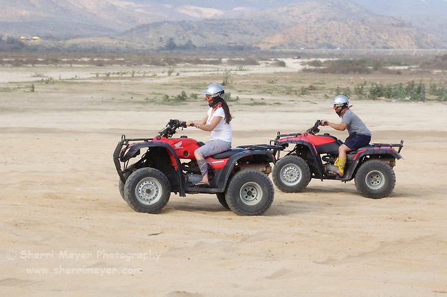Couple riding Quads on the playa near Migrino, Baja California, Mexico