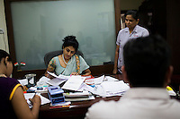 Dr. Nayana Patel (center), sits at her desk in her Akanksha IVF and surrogacy center that she founded with her husband, Dr. Hitesh, in Anand, Gujarat, India on 10th December 2012. She had done her first successful surrogacy birth in 2003, and has delivered over 565 babies since the clinic's establishment. When choosing surrogates, they are counseled, and screened following a stringent guideline. Surrogates must be married and have completed their own families with their own children, and the couple must be medically, physically, psychologically, emotionally and mentally sound. While 15% of couples are infertile globally, only 6% of infertility cases require surrogacy as a last option. Photo by Suzanne Lee / Marie-Claire France