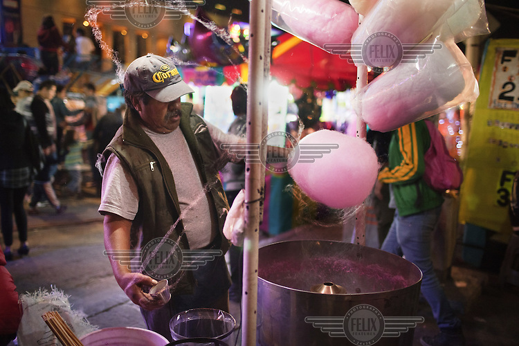 A man makes candy floss at a Christmas fair in the Alameda Central park.