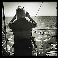 Sea Watch-2.<br /> Die Sea Watch-2 bei ihrer 13. SAR-Mission vor der libyschen Kueste.<br /> Im Bild: Ein Mitglied der Crew beobachtet mit dem Fernglass  ein Schlauchboot mit ca. 160 Menschen.<br /> 20.10.2016, Mediterranean Sea<br /> Copyright: Christian-Ditsch.de<br /> [Inhaltsveraendernde Manipulation des Fotos nur nach ausdruecklicher Genehmigung des Fotografen. Vereinbarungen ueber Abtretung von Persoenlichkeitsrechten/Model Release der abgebildeten Person/Personen liegen nicht vor. NO MODEL RELEASE! Nur fuer Redaktionelle Zwecke. Don't publish without copyright Christian-Ditsch.de, Veroeffentlichung nur mit Fotografennennung, sowie gegen Honorar, MwSt. und Beleg. Konto: I N G - D i B a, IBAN DE58500105175400192269, BIC INGDDEFFXXX, Kontakt: post@christian-ditsch.de<br /> Bei der Bearbeitung der Dateiinformationen darf die Urheberkennzeichnung in den EXIF- und  IPTC-Daten nicht entfernt werden, diese sind in digitalen Medien nach §95c UrhG rechtlich geschuetzt. Der Urhebervermerk wird gemaess §13 UrhG verlangt.]