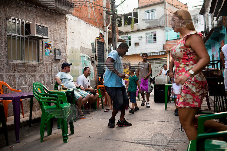 Residents enjoy a street party celebrating a birthday party in Complexo da Mare. The favela consists of a complex of 16 communities, in the north zone of Rio de Janeiro. It is the largest complex of favelas, housing 130,000 residents. It is targeted for pacification as the city prepares for the 2014 World Cup and the 2016 Olympics. Four factions run the complex, three drug gangs and the militia. The rival gangs fight for control of the drug trade. Although crime is low in the favelas by rule of law enforced by the gangs, cross-fire shootings and gang violence is often high. Neighborhood associations are an integral part of community development within Mare, making up for a lack of government assistance.