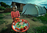 Ruth Mwautwa, 8, sells tomatoes in front of her family's house in Karonga, a town in northern Malawi where the ACT Alliance worked with local residents to recover from a 2009 earthquake.