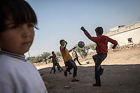 In this Sunday, Sep. 29, 2013 photo, Syrian children play football outside ABDU EL KADER (not pictured) family's house in Madaya village after attended classes in the public school in the Idlib province countryside of Syria. Children have come back to school in the rebel controlled territory despite the constant threaten of shelling and the ongoing fighting, and public schools still operating financially under the Syrian government administration. (AP Photo)