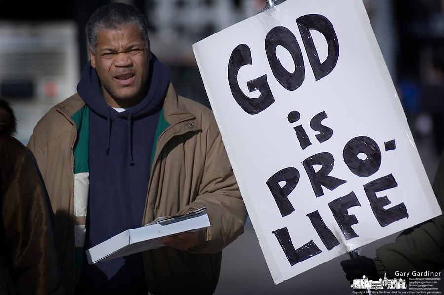A noontime pedestrian passes by a woman holding a Pro-Life sign at a rally at the Statehouse in Columbus, Ohio, Monday, Nov. 23, 2006, on the 33rd anniversary of the Supreme Court Roe v. Wade decision.<br />