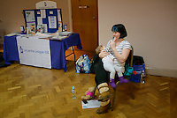 A mother breastfeeding her baby at a conference.<br /> <br /> Image from the breastfeeding collection of the &quot;We Do It In Public&quot; documentary photography picture library project: <br />  www.breastfeedinginpublic.co.uk<br /> <br /> <br /> Middlesex, England, UK<br /> 2016<br /> <br /> &copy; Paul Carter / wdiip.co.uk