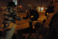 (L-r) Beauty Turner, Joseph Bakis, 38, Harold Hill, 34, and Grant Newburger, 50, a supporter of Bob Avakian's Revolutionary Communist Party, pass around 18 electric votives and paper cups to commemorate the number of people shot and killed by Chicago police officers in 2007 outside Chicago Police Headquarters on the corner of Michigan and 35th Street in Chicago, Illinois on December 20, 2007.