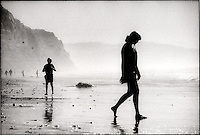 Silhouetted people walking along the beach<br />