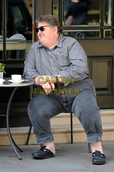 ROBBIE COLTRANE  .Spotted in Covent Garden, London, England..April 25th, 2010.*EXCLUSIVE ALL-ROUNDER*.full length sitting table drink beverage grey gray jeans denim shirt sunglasses shades clogs shoes .CAP/IA.©Ian Allis/Capital Pictures.