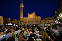 Diners eating al fresco at bar restaurant overlooking Il Torre del Mangia and Palazzo Publico, in Piazza del Campo, Siena, Italy RESERVED USE - NOT FOR DOWNLOAD - FOR USE CONTACT TIM GRAHAM