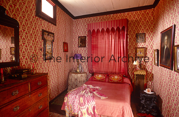Vibrant neo-gothic wallpaper lines the walls of this pretty bedroom creating a cosy jewel-box effect