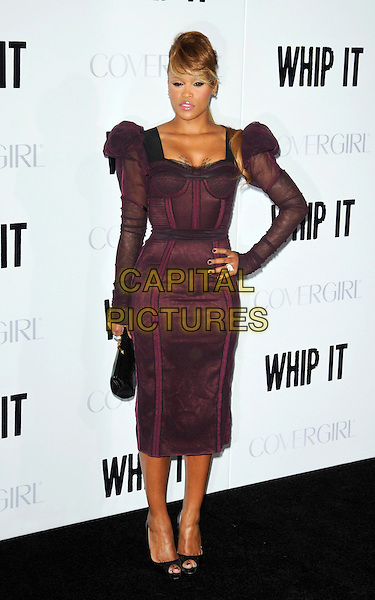 """EVE (Eve Jihan Jeffers).Attending the """"Whip It"""" Los Angeles Premiere held At Grauman's Chinese Theatre, Hollywood, California, USA, 29th September 2009..full length maroon burgundy red purple dress bustier puff sleeve shoulders long sleeved sleeves tattoos cleavage black clutch bag open toe shoes corset hand on hip.CAP/ROT.©Lee Roth/Capital Pictures"""