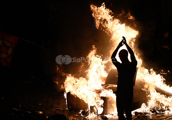 A protestor throws wood onto a fire during demonstrations against the G20 summit in Hamburg, Germany, 6 July 2017. The heads of the governments of the G20 group of countries are meeting in Hamburg on the 7-8 July 2017. Photo: Axel Heimken/dpa /MediaPunch ***FOR USA ONLY***
