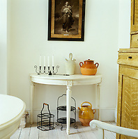 Earthenware pots and a candlestick on a white Swedish console table