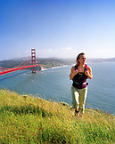 USA, California, Marin Headlands, woman hiking above the Golden Gate Bridge, with San Francisco in the distance
