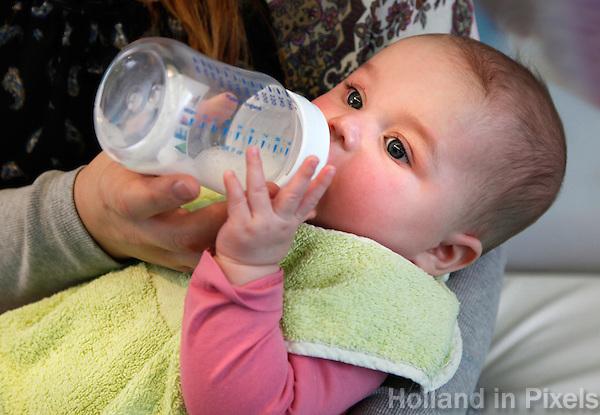 Baby drinkt een flesje melk