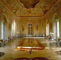 Ornate painted panels cover the walls of this pink and gold rococo ballroom and the ornate marquetry on the floor is the work of Antonio Rinaldi