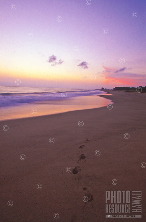 Waimea beach sunset with footprints in the sand, island of Kauai