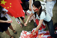 A woman sells Chinese flags and other nationalist items to spectators watching  the Nanjing, China, leg of the 2008 Olympic Torch Relay.  .
