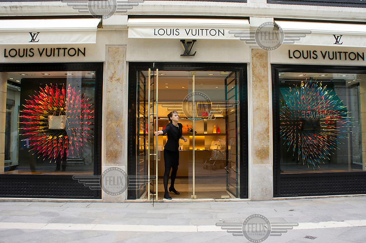An assistant closes the door to keep the riff-raff out of the Louis Vuitton shop near St Mark's Square.