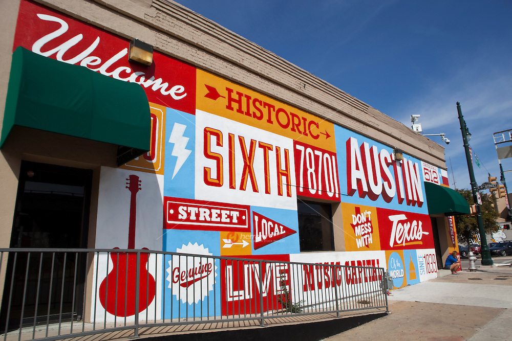 A Hand painted mural, Welcome to Historic Sixth Street, welcomes visitors to the historic 6th street entertainment district in Austin, Texas
