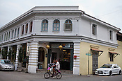 A cyclist rides past the restored heritage hotel, Straits in the UNESCO heritage town - Georgetown of Penang, Malaysia. Photo: Sanjit Das/Panos