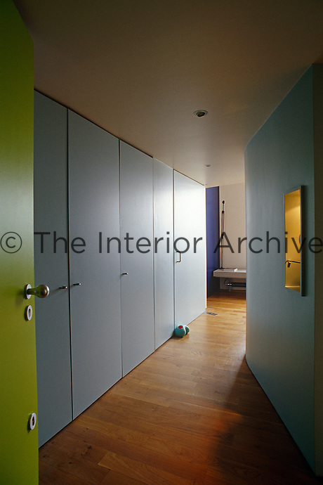The lime green front door opens onto a row of floor-to-ceiling cupboards in the entrance hallway