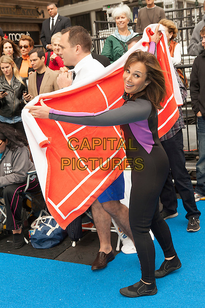 Greg Kelly, Rosanna Scotto<br /> attends the 'Swim for Relief' Benefiting Hurricane Sandy Recovery at Herald Square, New York City, NY., USA.<br /> October 9th, 2013 <br /> full length black wetsuit red flag looking over shoulder jacket<br /> CAP/MPI/COR<br /> &copy;Corredor99/ MediaPunch/Capital Pictures