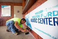 NWA Democrat-Gazette/JASON IVESTER<br /> Brock Pollard with Arkansas Sign & Banner installs a new sign Friday, May 26, 2017, at the Melvin Ford Aquatic Center in Bentonville. The pool opens for the season today (SATURDAY).