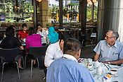 People gather for a meeting at a cafe outside the KLCC twin towers in Kuala Lumpur, Malaysia. Photo: Sanjit Das/Panos