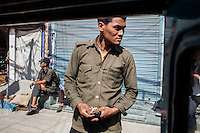 A bus ticket conductor in front of a bus on the streets Kathmandu. 01 May 2013, © Nicolas Axelrod 2013