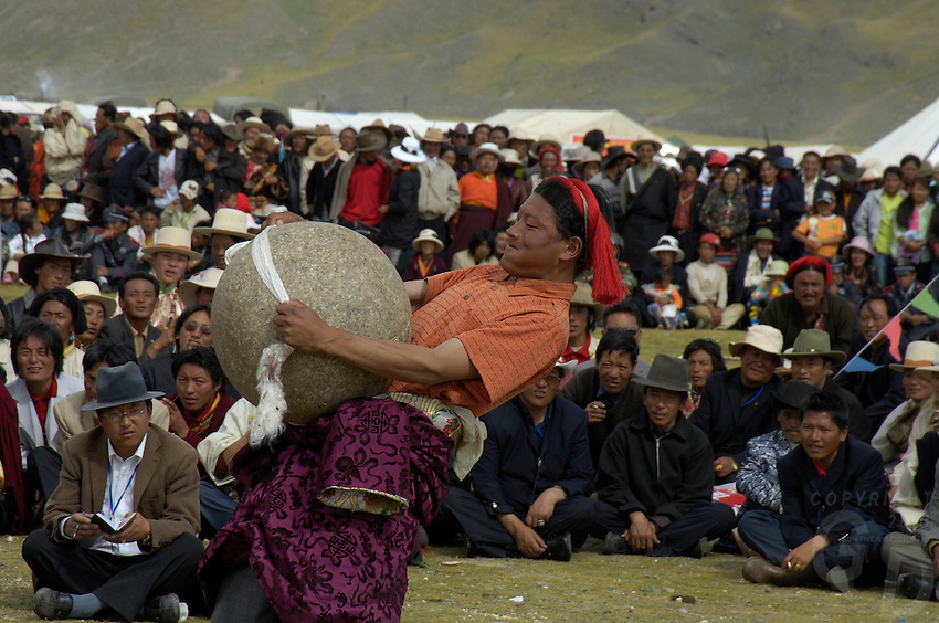 Strngman competition, lifting a round boulder with only a scarf..Traditional Tibetan dress up in their finest and wearing their most precious Jewelry during this festival. The most common gem stones are worn in the jewelry are Turquoise and red coral..Changtang Chachen Horse Race Festival (August 10th) is the most important festival in northern Tibet during the golden season on the grassland. Thousands of herdsmen throng to Nakchu riding fine horses and carrying local products. They erect a tent city south of Nakchu town. They celebrate with a thrilling horse race, archery contests, and demonstrations of horsemanship. Song-and-dance troupes from all parts of Tibet add to the festivity. It is said that this is the highest horse racing festival in the world, at 4800 meters.