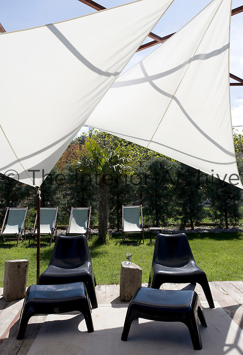 Black plastic chairs and footstools beneath a sail-like awning on the terrace