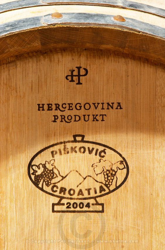 Oak barrel with stamp saying the winery's name and that the barrel is made from Croatian oak, Piskovic Croatia. Hercegovina Produkt winery, Citluk, near Mostar. Federation Bosne i Hercegovine. Bosnia Herzegovina, Europe.