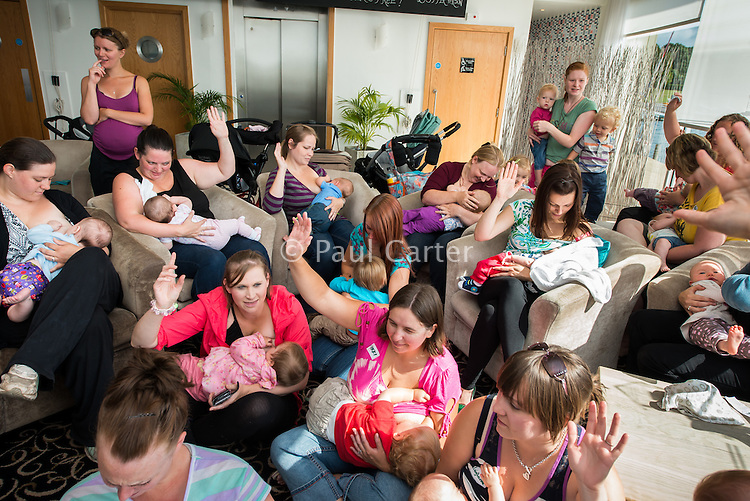 A group of mothers from Poole area all breastfeeding their babies at the same time raise their hands to be counted in The Big Latch On breastfeeding promotion event At Sevens Boat-house restaurant and cafe in Poole Park, Poole Dorset. The women were largely from Poole Bosom Buddies drop-in breastfeeding support centre - http://abm.me.uk/support-group/poole-bosom-buddies/<br /> <br /> 02/08/2013<br /> <br /> The Big Latch On http://biglatchon.org is an annual event to mark World Breastfeeding Week - http://worldbreastfeedingweek.org .<br /> <br /> &quot;Groups of breastfeeding women coming together at registered locations around the world to all latch on their child at a set time. All the breastfeeding women and children are latched on for one minute at the set time and are counted by the witnesses. The numbers are added up and we see if we can beat previous Big Latch On records! &quot;<br /> <br /> Image from the &quot;We Do It In Public&quot; breastfeeding documentary photography picture library project: <br />  www.breastfeedinginpublic.co.uk<br /> <br /> <br /> Dorset, England, UK<br /> 02/08/2013<br /> <br /> &copy; Paul Carter / wdiip.co.uk