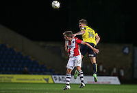 Josh Ruffels of Oxford United beats Max Smallcombe of Exeter City in the air during the The Checkatrade Trophy match between Oxford United and Exeter City at the Kassam Stadium, Oxford, England on 30 August 2016. Photo by Andy Rowland / PRiME Media Images.