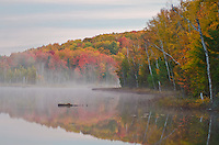 Morning light shows the mist rising off the waters of Council Lake in the Hiawatha National Forest in Alger County, Michigan