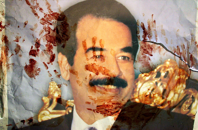 Baghdad, October 22, 2002..Ex-prisoners amnistied 2 days previously from their jails by an unprecedented presidential decree claim their support to Saddam Hussein..Demonstrators express their willingness to give their blood to defend Iraq and their president against an eventual US-led strike by imprinting their hands on Saddam Hussein posters with their blood.