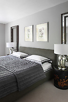 A pair of bedside lamps with a tarnished mirror finish stand on either side of the upholstered bed in this bedroom