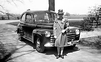 A woman stands next to her 1940's era automobile.  (Photo by www.bcpix.com)