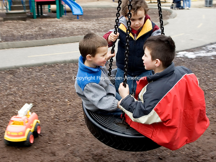 PROSPECT, CT- 13 MARCH 07- 031307JT04- <br /> Brendan Healy and John Marchetti, both 3, listen to five-year-old Desmond Mamudi as they share a ride on the tire swing at the playground at Hotchkiss Park in Prospect on Tuesday.<br /> Josalee Thrift Republican-American
