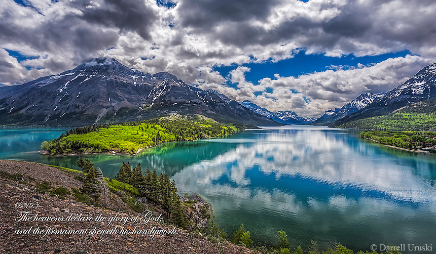 Fine Art Scenic of Waterton Lakes National Park in Alberta, Canada. This location is a world heritage site that boarders Canada and the USA. <br /> The morning clouds were reflecting onto the cool blue still waters of this mountain lake. The shoreline also reflecting their emerald colours  onto the cool mountain water of this spectacular location. <br /> This fine art scenic also includes the bible scripture verse Psalm 19:1 The heavens declare the glory of God; and the firmament sheweth his handywork.